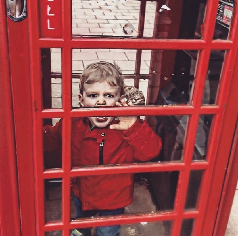 A toddler having a tantrum in a phone box