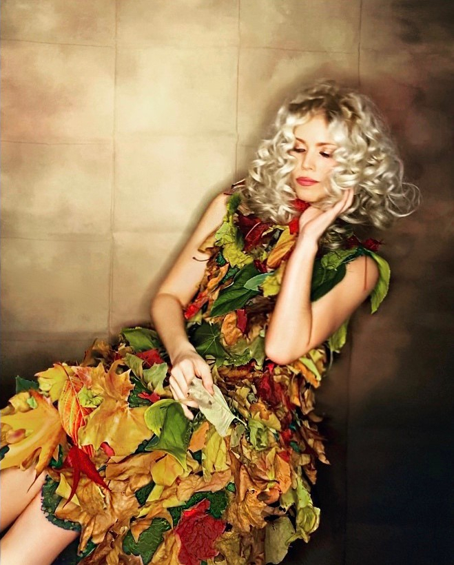 A beautiful woman wearing an autumn dress made out of leaves.