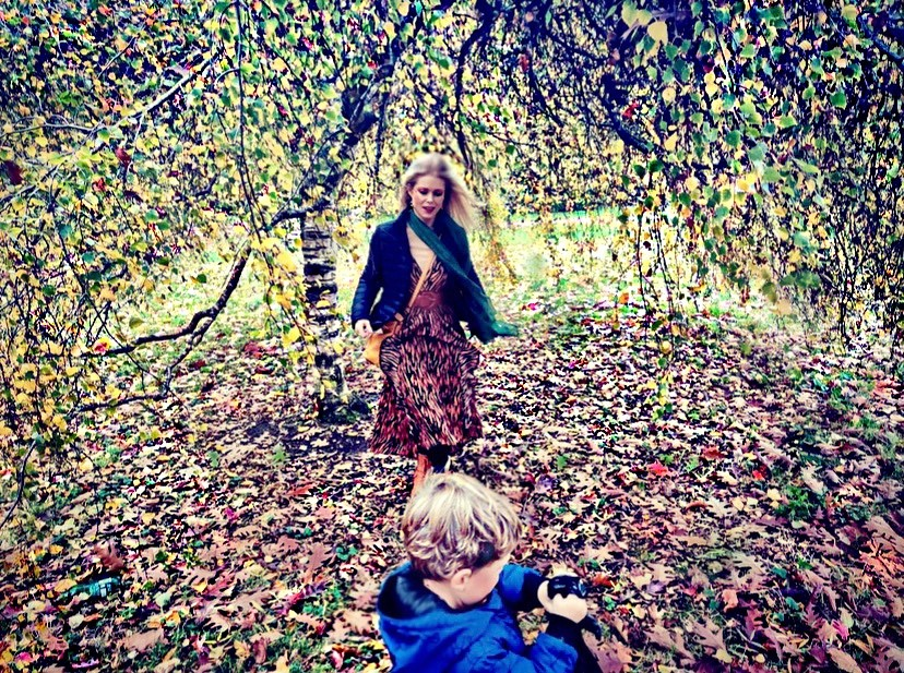 A woman walking in stunning colourful Autumn leaves and trees with toddler